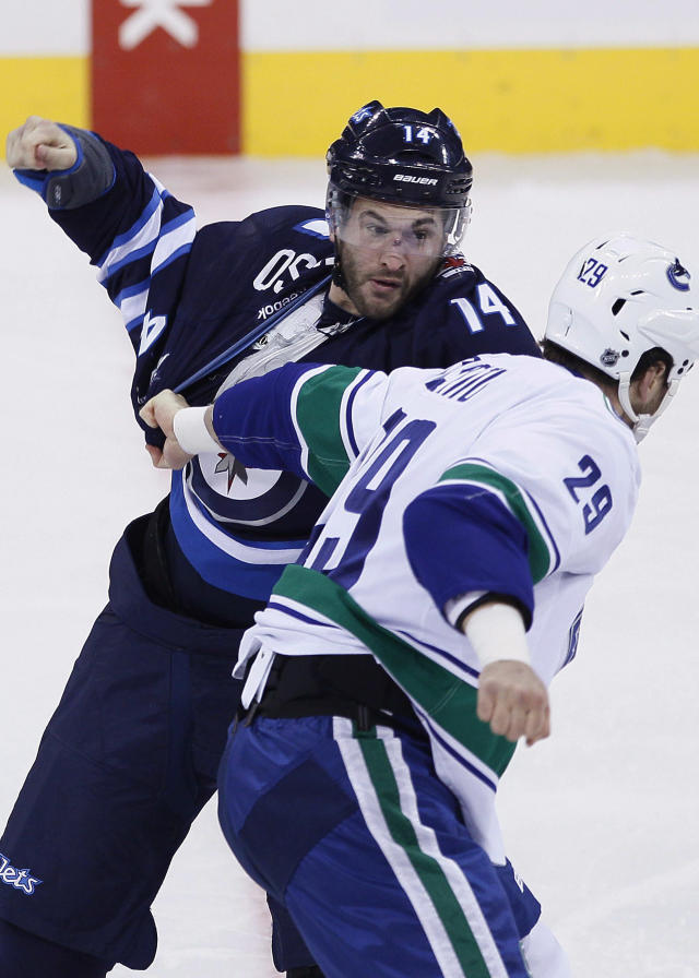Winnipeg Jets' Anthony Peluso (14) and Vancouver Canucks' Tom Sestito (29) fight during the first period of an NHL hockey game Wednesday, March 12, 2014, in Winnipeg, Manitoba. (AP Photo/The Canadian Press, John Woods)