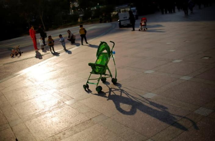FILE PHOTO: A baby stroller is seen as mothers play with their children at a public area in downtown Shanghai