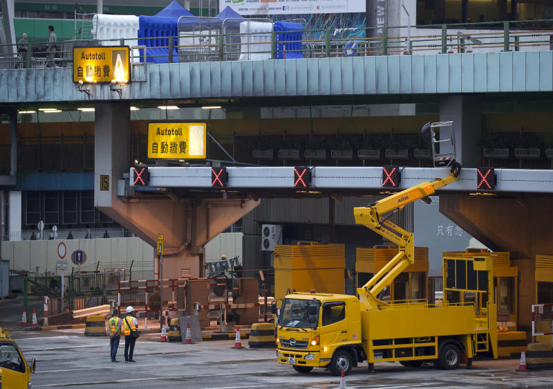 Workers repair tollbooths for the Cross-Harbour Tunnel near the Hong Kong Polytechnic University in Hong Kong, Tuesday, Nov. 26, 2019. A weeklong police siege of a university in Hong Kong may be winding down, closing one of the more violent chapters in the city's long-running anti-government protests. (AP Photo/Ng Han Guan)
