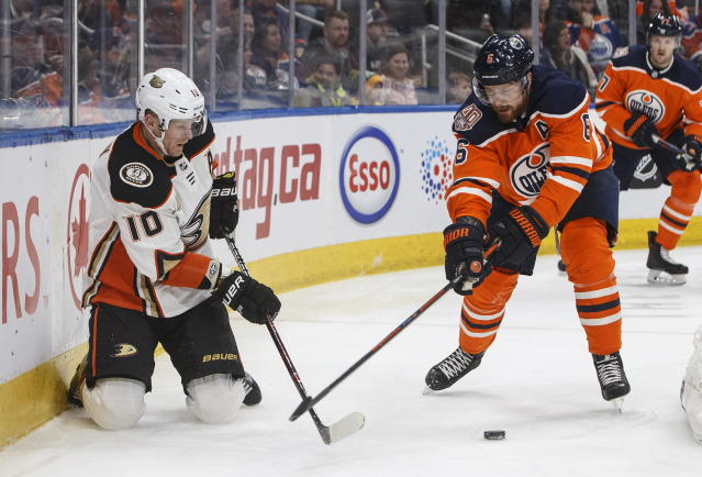 Anaheim Ducks' Corey Perry (10) and Edmonton Oilers' Adam Larsson (6) vie for the puck during the first period of an NHL hockey game Saturday, Feb. 23, 2019, in Edmonton, Alberta. (Jason Franson/The Canadian Press via AP)