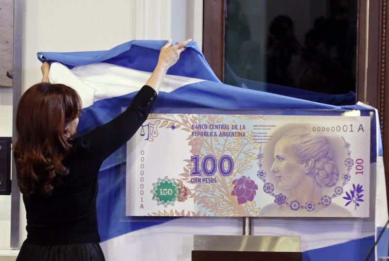 """FILE - In this July 25, 2012 photo, Argentina's President Cristina Fernandez unveils an archetype of the new 100 Argentine pesos bill bearing the profile of former late first lady Maria Eva Duarte de Peron, better known as """"Evita,"""" at the government palace in Buenos Aires, Argentina. Judgment day is approaching in an epic battle between Argentina and New York billionaire Paul Singer, who has sent lawyers around the globe trying to force the South American country to pay its defaulted debts. Three U.S. appellate judges will hear oral arguments in New York on Wednesday, Feb. 27, 2013, in the case, NML Capital Ltd. v. Argentina. The case has shaken bond markets, worried bankers, lawyers and diplomats, captivated financial analysts and generated enough """"friend of the court"""" briefs to kill a small forest. (AP Photo/Alberto Raggio, DyN, File)"""