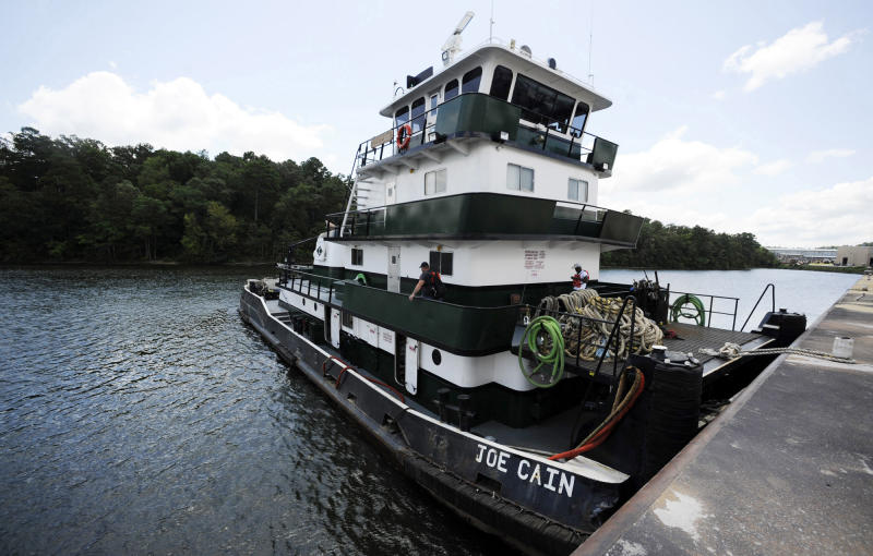 In this Tuesday, July 23, 2019 photo, crew members aboard the Mobile, Ala.-based tugboat Joe Cain prepare to depart the Yellow Creek State Inland Port on the Tennessee-Tombigbee Waterway at Iuka, Miss. The waterway hasn't lived up to expectations in terms of barge traffic or economic development in parts of Alabama and Mississippi, but the port provides jobs and helps the economy in Iuka, located near the Tennessee line. (AP Photo/Jay Reeves)