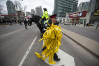 <p>A police officer smiles as he walks off with used police tape after the partial opening of Yonge Street at Finch Avenue on April 24, 2016 in Toronto. Cole Burston/Getty Images </p>