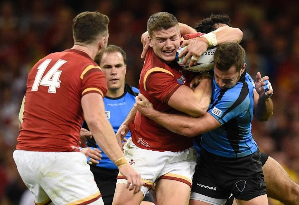 Wales' Scott Williams (C) is tackled by Uruguary's Felipe Berchesi during the Rugby World Cup Pool A match at the Millennium Stadium on September 20, 2015 (AFP Photo/Martin Bureau)