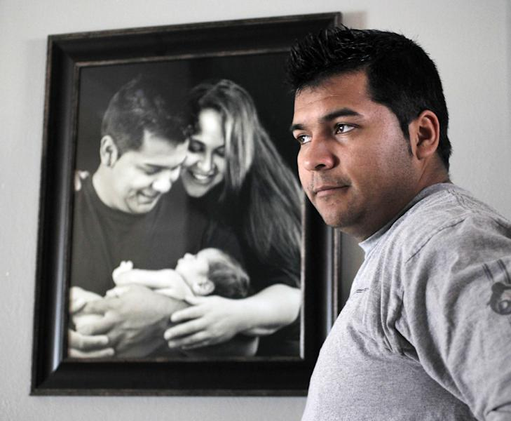 UPDATES CAPTION INFORMATION - FILE - In this Friday, Jan. 3, 2014 file photo, Erick Munoz stands with an undated copy of a photograph of himself, left, with wife Marlise and their son Mateo, in Haltom City, Texas. Marlise was removed from life support Sunday, Jan. 26, 2014, as the hospital keeping her on machines against her family's wishes acceded to a judge's ruling that it was misapplying state law. . (AP Photo/The Fort Worth Star-Telegram, Ron T. Ennis, File) MANDATORY CREDIT