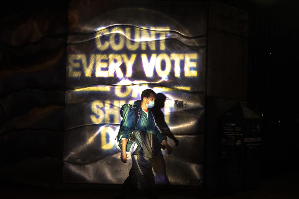 A man walks through a projected election slogan during protests following the Nov. 3 presidential election in Portland, Or. Wednesday, Nov. 4, 2020. (AP Photo/Paula Bronstein)