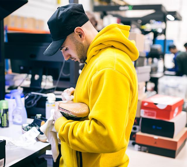 A StockX authenticator inspecting a product at the company's London facility. Photo: StockX