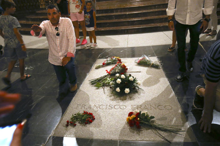 A man salutes as he stands next to the tomb of former Spanish dictator Francisco Franco inside the basilica at the the Valley of the Fallen monument near El Escorial, outside Madrid on Friday, Aug. 24, 2018. Spain's center-left government has approved legal amendments that it says will ensure the remains of former dictator Gen. Francisco Franco can soon be dug up and removed from a controversial mausoleum. (AP Photo/Andrea Comas)