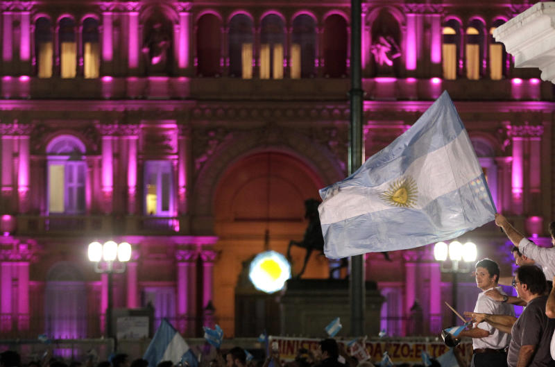 People bang pots and hold an Argentine flag, right, in front of the government house, background, during a march against Argentina's President Cristina Fernandez in Buenos Aires, Argentina, Thursday, Nov. 8, 2012. Angered by rising inflation, violent crime and high-profile corruption, and afraid Fernandez will try to hold onto power indefinitely by ending constitutional term limits, the protesters banged pots and marched in Argentina's capital. Protests also were held in plazas nationwide and outside Argentine embassies and consulates around the world. (AP Photo/Victor R. Caivano)