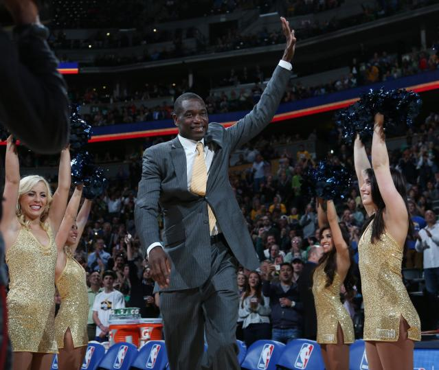Former Denver Nuggets center Dikembe Mutombo waves to crowd as he is introduced during halftime ceremony to honor the players and coaches on the 1994 Denver team that upset top-seed Seattle SuperSonics in the opening round of the NBA Playoffs on Monday, March 17, 2014, in Denver. The ceremony was staged during halftime of the Nuggets' 110-100 victory over the Los Angeles Clippers. (AP Photo/David Zalubowski)