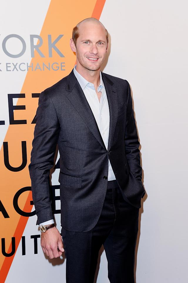 "Alexander Skarsgård wearing his new 'do and a dark gray suit at the Louis Vuitton ""Voyez, Voguez, Voyagez"" event red carpet Thursday night in New York. (Photo: Getty Images)"