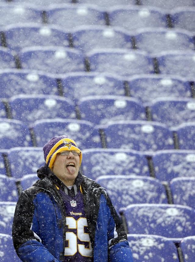 A Minnesota Vikings fan tries to catch snowflakes on his tongue as he watches players warm up before an NFL football game between the Vikings and the Baltimore Ravens, Sunday, Dec. 8, 2013, in Baltimore. A powerful storm system that spread snow, sleet and freezing rain widely across the nation's midsection rumbled toward the densely populated Eastern seaboard on Sunday, promising more of the same. (AP Photo/Patrick Semansky)