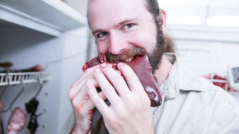 Man with ponytail biting into raw meat