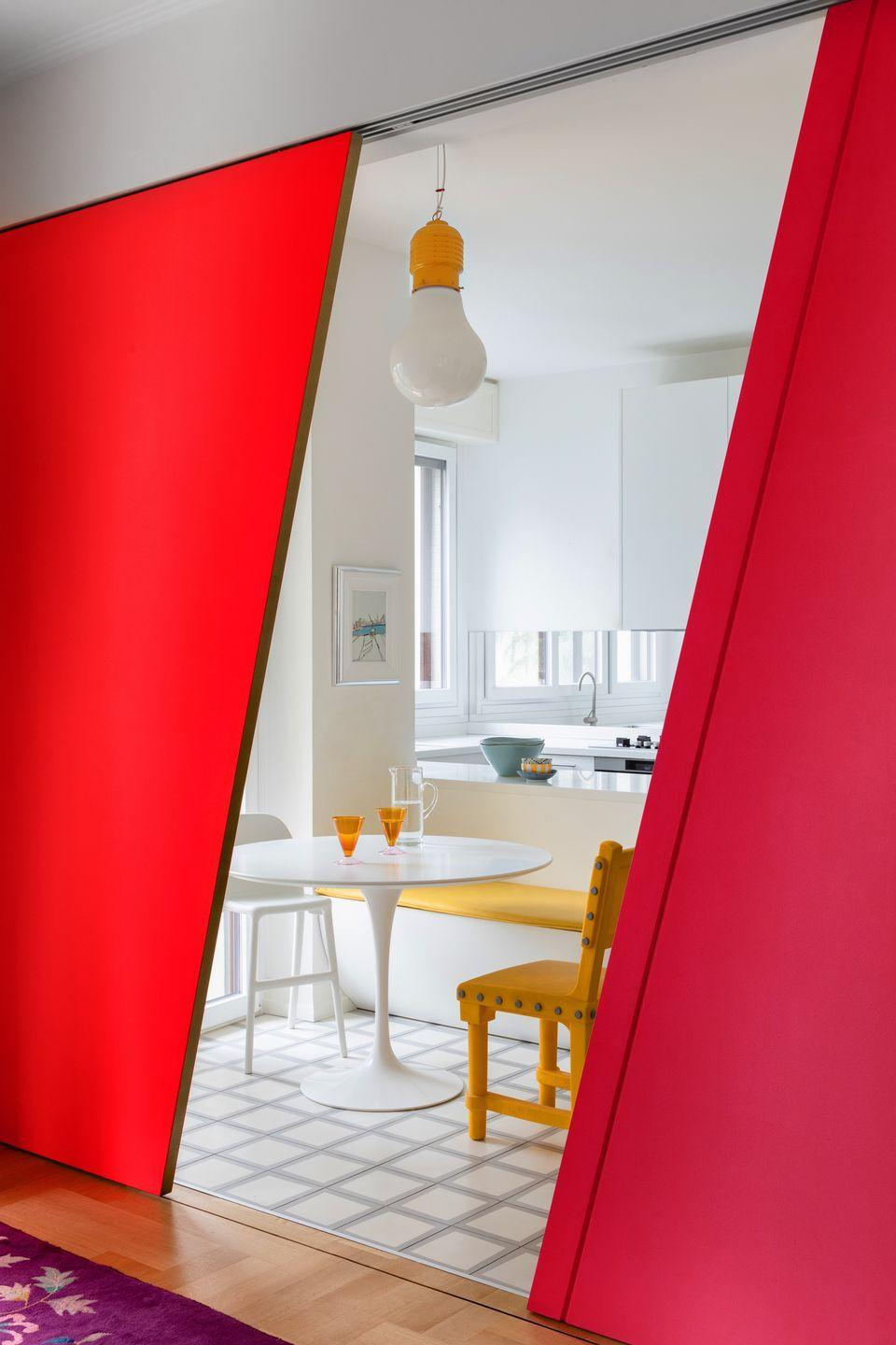 """<p>If committing your cabinetry to colour is a step too far, consider framing your kitchen in colour via adjoining walls, dividers and doors instead. The bolder the better – this punchy red screen adds a whole new perspective to the white kitchen in interior designer <a href=""""https://elledecoration.co.uk/houses/a34359655/colourful-milan-home-patricia-bohrer/"""" rel=""""nofollow noopener"""" target=""""_blank"""" data-ylk=""""slk:Patricia Bohrer's Milan home"""" class=""""link rapid-noclick-resp"""">Patricia Bohrer's Milan home</a>.</p>"""