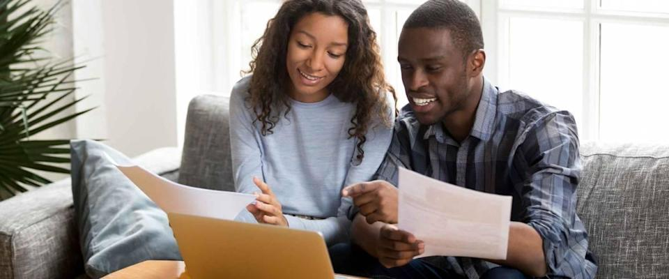 Black married couple sitting on sofa looking at papers and computer
