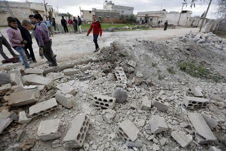Residents inspect damaged ground after a shell fell in the rebel held town of Jarjanaz, southern Idlib countryside