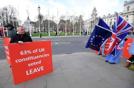 Pro-Brexit and anti-Brexit protesters stand outside of the Houses of Parliament, in London, Britain