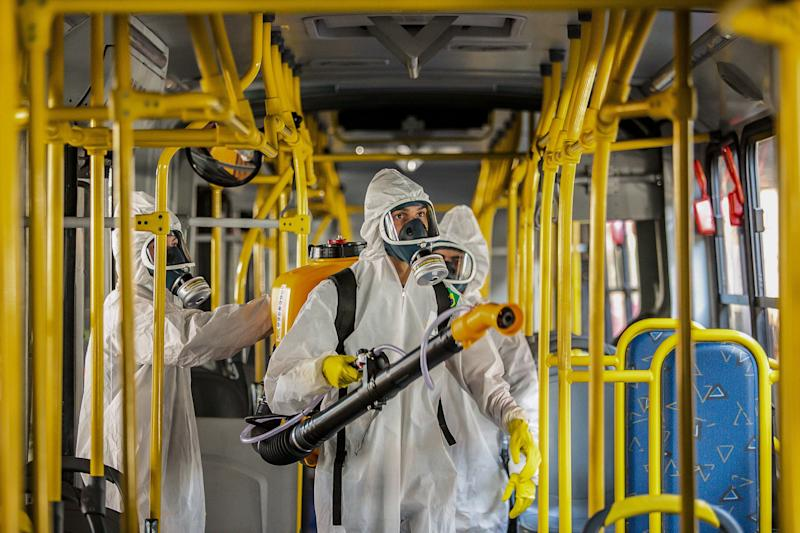 Military personnel from the Brazilian Armed Forces sanitize a bus at the Santa Candida bus terminal to combat the spread of the the novel coronavirus, COVID-19, in Curitiba, Parana State, Brazil, on August 10, 2020. - The pandemic has killed at least 731,518 people worldwide, 101,049 of them in Brazil, since it surfaced in China late last year, according to a tally from official sources compiled by AFP at 1100 GMT on Monday. (Photo by Daniel CASTELLANO / AFP) (Photo by DANIEL CASTELLANO/AFP via Getty Images)