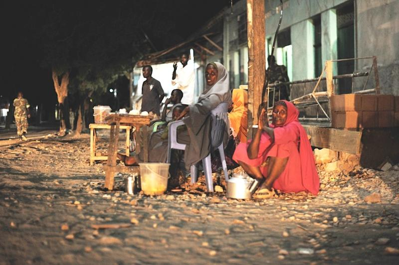 Somali women sell tea on the side of the road in Baidoa on June 22, 2014, while Ethiopian soldiers in the African Union Mission in Somalia conduct a night patrol (AFP Photo/)