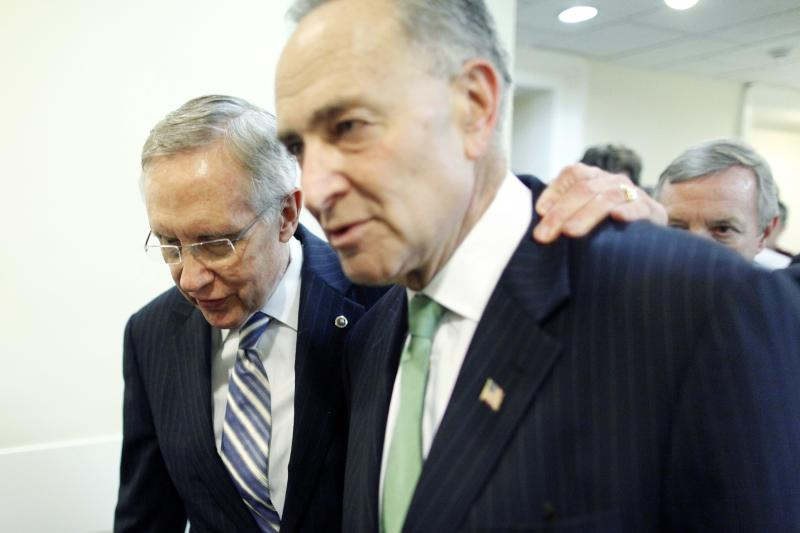 Reid walks with his arm around Schumer as they depart following a news conference in Washington