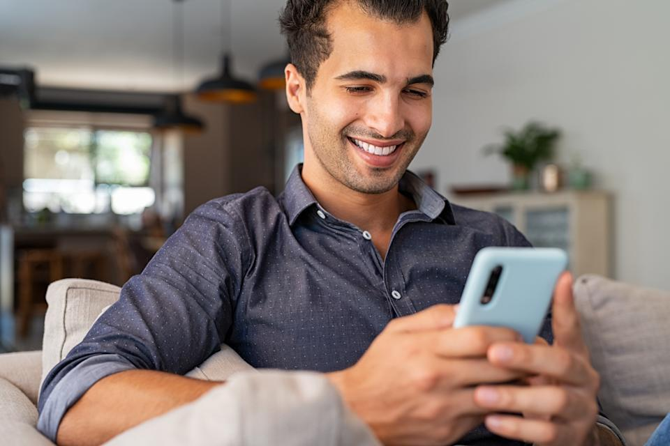Cheerful businessman using smartphone while sitting on sofa at home. Handsome young indian man sitting on couch reading messages on mobile phone. Hispanic guy working from home with cellphone.