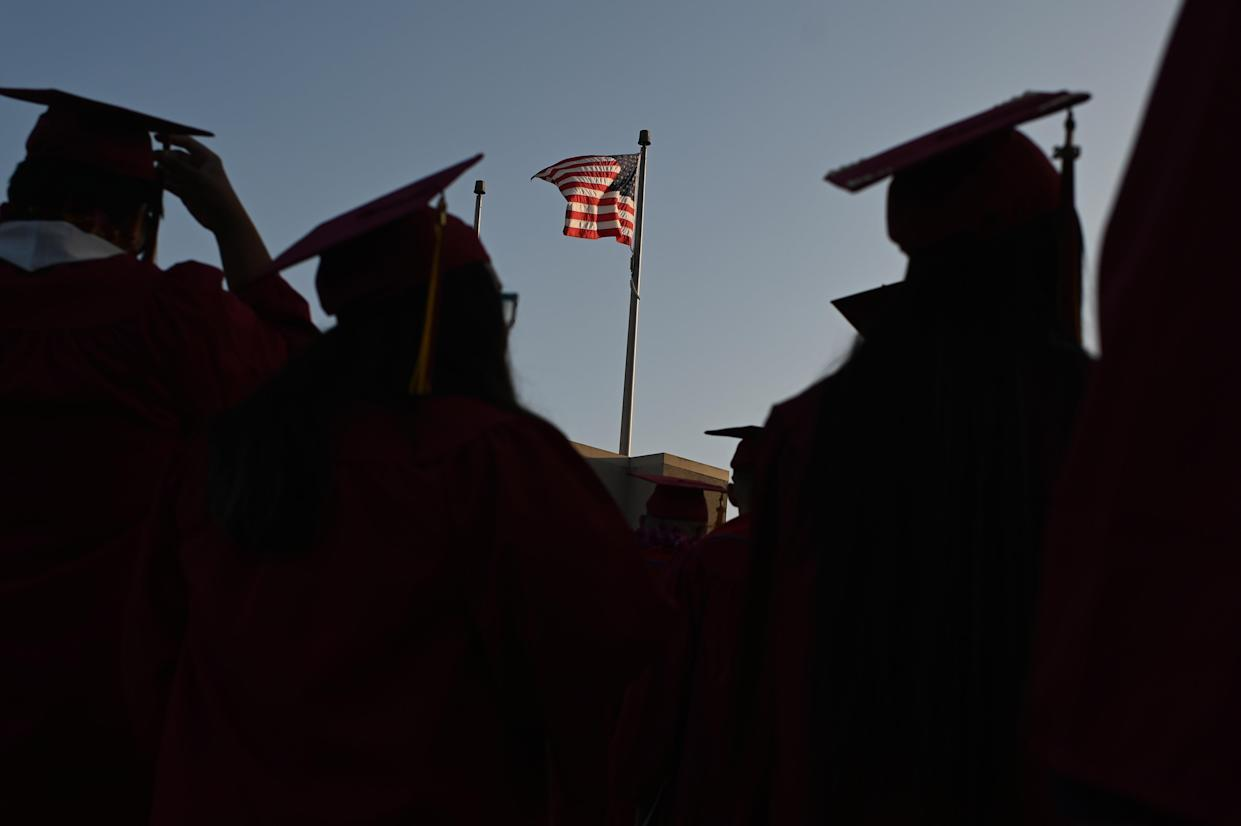 A US flag flies above a building as students earning degrees at Pasadena City College participate in the graduation ceremony, June 14, 2019, in Pasadena, California. (Photo by Robyn Beck / AFP) (Photo credit should read ROBYN BECK/AFP/Getty Images)