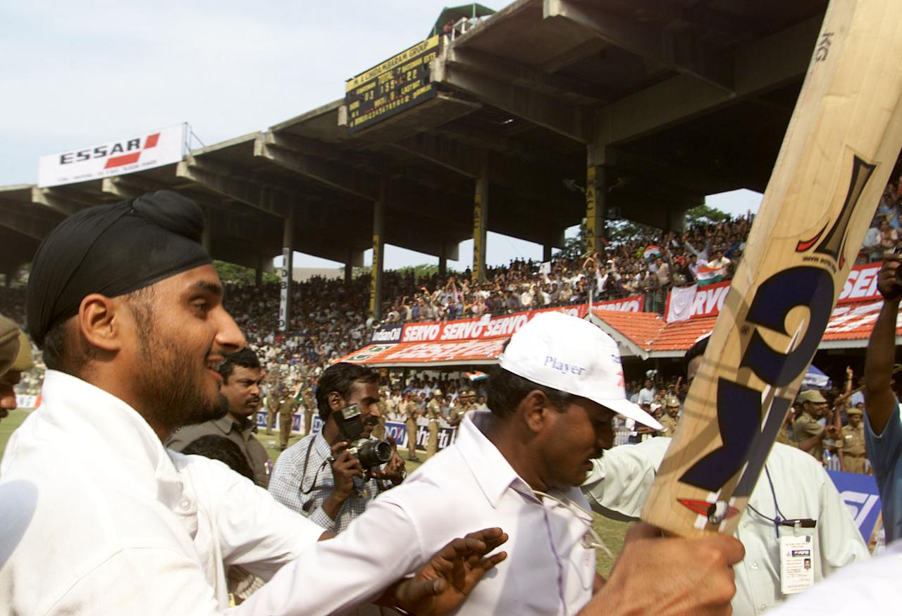 22 Mar 2001:  Harbhajan Singh of India is escorted from the field after hitting the winning runs, during day five of the third test between India and Australia at the M.A. Chidambaram Stadium, Chennai, India. India won the Test by two wickets and the series 2 -1  X DIGITAL IMAGE  Mandatory Credit: Hamish Blair/ALLSPORT