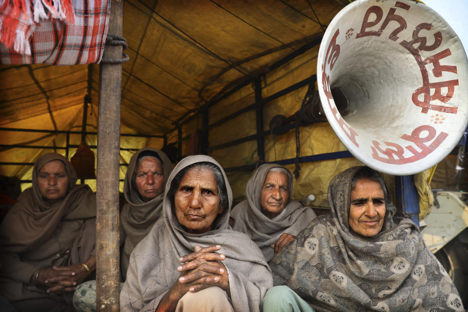 Elderly women farmers sit at the back of a trailer as they participate in a protest against new farm laws at the Delhi-Haryana state border, on the outskirts of New Delhi, India, Sunday, Dec. 27, 2020. From students, teachers and nurses to housewives and grandmothers, women are now holding the front lines at the massive protests that have blockaded key highways leading to India's capital for more than a month, demanding the repeal of new farm laws. (AP Photo/Manish Swarup)