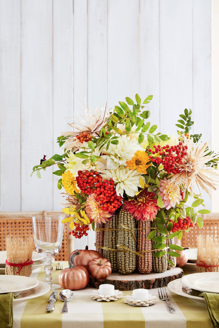 """<p>It's not Thanksgiving without at least a few cobs of corn. Coated with metallic paint and placed around a lush bouquet, the holiday staple feels fresh, original, and inspired.</p><p><strong>To make: </strong>Coat roughly 14 cobs of dried corn with metallic gold and copper <a href=""""https://www.amazon.com/Krylon-K05588007-COLORmaxx-Spray-Aerosol/dp/B07LFWTSP8?tag=syn-yahoo-20&ascsubtag=%5Bartid%7C10050.g.2063%5Bsrc%7Cyahoo-us"""" rel=""""nofollow noopener"""" target=""""_blank"""" data-ylk=""""slk:spray paint"""" class=""""link rapid-noclick-resp"""">spray paint</a>. Once dry, hot-glue cobs to the perimeter of a 6-inch round vase. Tie it all together with <a href=""""https://www.amazon.com/Natural-Paper-Raffia-Ribbon-Metallic/dp/B071WLDNMZ?tag=syn-yahoo-20&ascsubtag=%5Bartid%7C10050.g.2063%5Bsrc%7Cyahoo-us"""" rel=""""nofollow noopener"""" target=""""_blank"""" data-ylk=""""slk:gold raffia"""" class=""""link rapid-noclick-resp"""">gold raffia</a>. Fill vase with <a href=""""https://www.amazon.com/FloraCraft-Special-Flores-Original-Version/dp/B001FD5EZW?tag=syn-yahoo-20&ascsubtag=%5Bartid%7C10050.g.2063%5Bsrc%7Cyahoo-us"""" rel=""""nofollow noopener"""" target=""""_blank"""" data-ylk=""""slk:floral foam"""" class=""""link rapid-noclick-resp"""">floral foam</a> and add seasonal flowers as desired. (This sampling includes dahlias, zinnias, and mountain ash berries.)</p><p><a class=""""link rapid-noclick-resp"""" href=""""https://www.amazon.com/Just-Ear-Corn-8LBS-Iowa/dp/B07KDXMBHK/ref=sr_1_16?tag=syn-yahoo-20&ascsubtag=%5Bartid%7C10050.g.2063%5Bsrc%7Cyahoo-us"""" rel=""""nofollow noopener"""" target=""""_blank"""" data-ylk=""""slk:SHOP DRIED CORN"""">SHOP DRIED CORN</a></p>"""