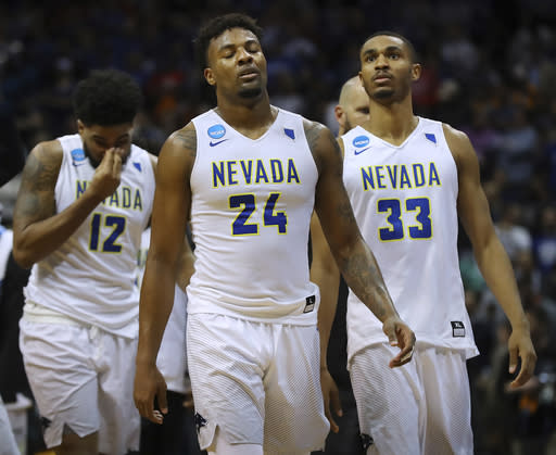 Nevada's Elijah Foster, Jordan Caroline, and Josh Hall, from left, walk off the court after the team's 69-68 loss to Loyola-Chicago during an NCAA men's college basketball tournament regional semifinal Thursday, March 22, 2018, in Atlanta. (Curtis Compton/Atlanta Journal-Constitution via AP)