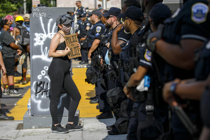 """FILE - In this June 23, 2020 file photo, A woman holds up a sign saying """"police the police"""" as she confronts a police line while demonstrators protest in Washington, over the death of George Floyd. Without major changes in almost every state, a national police misconduct database like what the White House and Congress have proposed after George Floyd's death would fail to account for thousands of problem officers.(AP Photo/Jacquelyn Martin File)"""