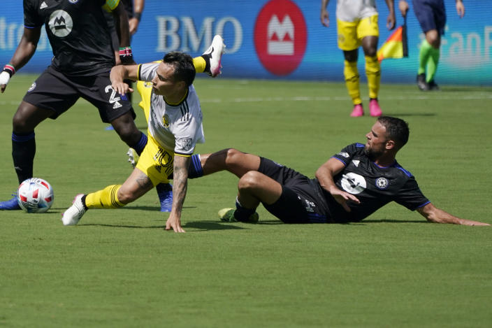 Columbus Crew midfielder Lucas Zelarayan, left, falls to the field as he goes for the ball against CF Montréal defender Rudy Camacho during the first half of an MLS soccer match, Saturday, May 1, 2021, in Fort Lauderdale, Fla. (AP Photo/Lynne Sladky)