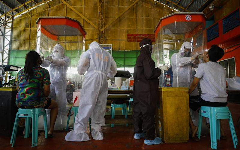 Wearing protective suits, Philippine police who are also registered nurses collect swab samples from citizens for SARS-CoV-2 testing - ROLEX DELA PENA/EPA-EFE/Shutterstock