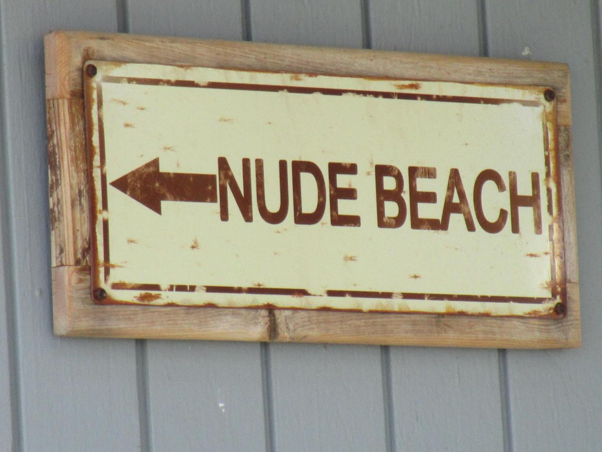 """A metal sign attached to a piece of wood hung up on gray wall that says written in brown letters with an arrow, """"NUDE BEACH"""" on a beige background."""