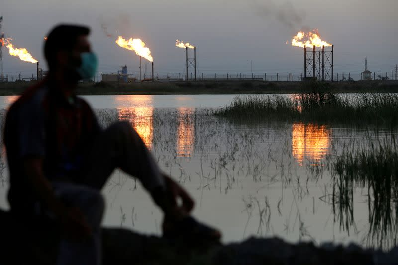 FILE PHOTO: Flames emerge from flare stacks at Nahr Bin Umar oil field, as a man is seen wearing a protective face mask , following the outbreak of the coronavirus, north of Basra