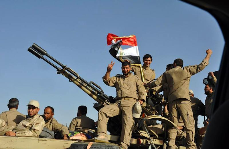 Iraqi forces and mainly Shiite Muslim volunteers arrive in the predominantly-Sunni Muslim city of Samarra, 124 kms from Baghdad, on July 2, 2014, to protect the Shiite Muslim Al-Askari shrine