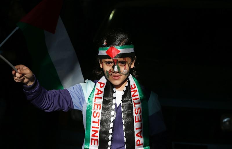An Arab Israeli girl waves the Palestinian flag during a rally commemorating Land Day on March 30, 2016 in the northern Israeli village of Arrabe