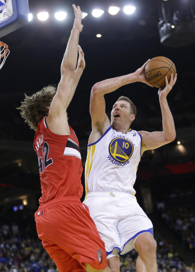 In this Jan. 26, 2014, photo, Golden State Warriors' David Lee (10) shoots over Portland Trail Blazers' Robin Lopez during an NBA basketball game in Oakland, Calif. Lee says he has damage in the nerve that connects from his back to his right hamstring but hopes to be back for the playoffs--if not sooner. Lee participated in some of Wednesday's light practice on April 9, 2014, working up a sweat on his gray shirt before shooting free throws during the portion open to reporters. He has missed six straight games and is expected to sit out again Thursday night against Denver. (AP Photo/Marcio Jose Sanchez)
