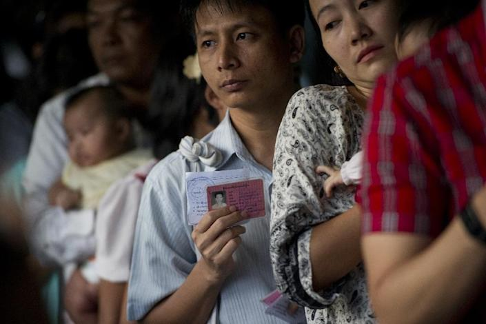 A man holds his identity card for voting at a polling station in Yangon on November 8, 2015 (AFP Photo/Ye Aung Thu)