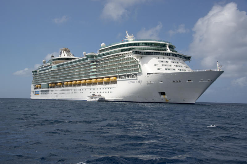 The Royal Caribbean Freedom of the Seas, which carries 4,515 passengers and 1,360 crew, and the Celebrity Reflection, which carries 3,609 passengers and 1271 crew, in the harbor of George Town, Grand Cayman in the Cayman Islands on Tuesday, December 20, 2016. The smaller boat is a tender to ferry passengers back and forth to the island. Credit: Ron Sachs / CNP *** Please Use Credit from Credit Field ***