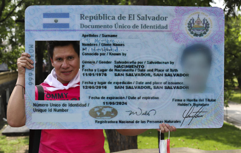 Wilson Escobar poses for a photo with a giant cutout of ID card, prior to the start of of an event marking International Day Against Homophobia in San Salvador, El Salvador, Monday, May 17, 2021. Since 1993 in El Salvador, a country of only 6.5 million inhabitants, more than 600 LGBTQ people have been killed. (AP Photo/Salvador Melendez)