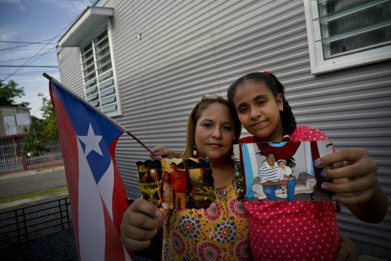 In this Sept. 5, 2018 photo, Lady Diana Torres, left, and her daughter Paula Nicole Lopez, pose with photos of their late husband and father Orlando Lopez Martinez, in Aguadilla, Puerto Rico. Lopez, who died at age 48 on Oct. 10, developed diabetes when he was 11, forcing him to begin dialysis. The center where he received dialysis shut down after Hurricane Maria hit, and after missing some treatments over more than a week, the center rationed his dialysis, according to friends and family. The official cause of death was a heart attack brought on by kidney disease. (AP Photo/Ramon Espinosa)