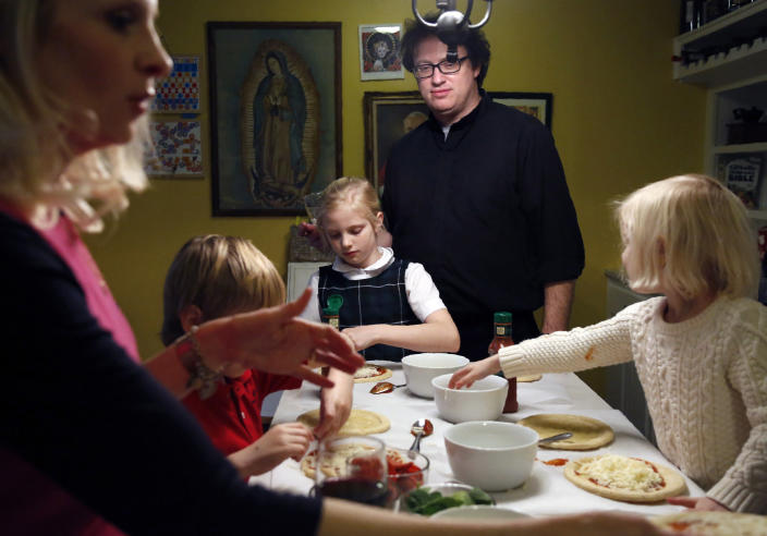 In this Feb. 7, 2020, photo, the Whitfield family, from left, wife Alli, son Peter, 8, daughter Maggie, 9, Father Joshua, and daughter Bernadette, 4, make individual pizzas at their home in north Dallas. (AP Photo/Jessie Wardarski)