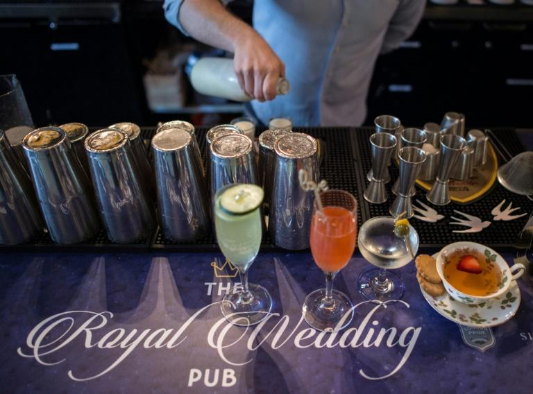 A bartender crafts drinks at a royal wedding-themed pop-up bar, where the menu includes a gin martini that's queen-approved