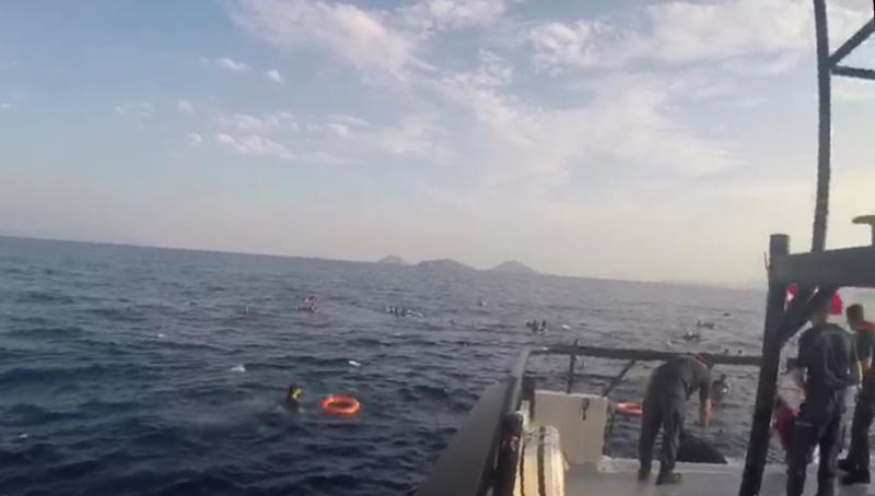 In this image taken from video made available by the Turkish Coastguard on Monday June 17, 2019, a coast guard boat approaches migrants in the Aegean Sea. A boat carrying migrants to Greece sank off the Turkish coast on Monday leaving at least eight migrants dead Turkey's coast guard said. The coast guard said 31 other migrants were rescued after the boat sank in the Aegean Sea, off the coast of Bodrum. (Turkish Coastguard via AP)