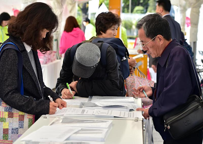 South Korean elderly people fill out application forms for employment, at a job fair in Seoul, on October 22, 2014 (AFP Photo/Jung Yeon-Je)