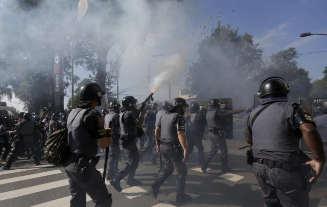 Riot policemen fire tear gas at demontrators during a protest against the 2014 World Cup in Sao Paulo June 12, 2014. REUTERS/Ricardo Moraes (BRAZIL - Tags: SPORT SOCCER WORLD CUP CIVIL UNREST)