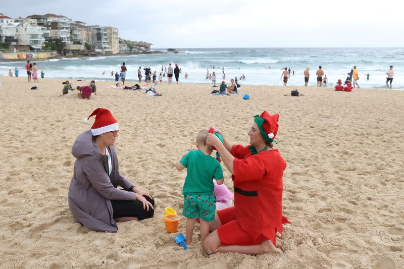 People wearing Christmas-themed attire spend time on Christmas Day at Bondi Beach in Sydney