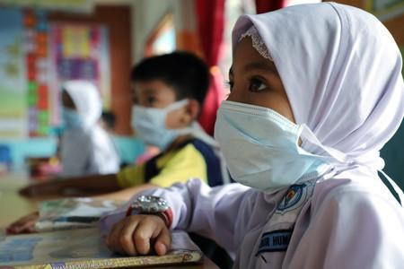 Students cover their faces with masks at a school as haze shrouds Kuala Lumpur