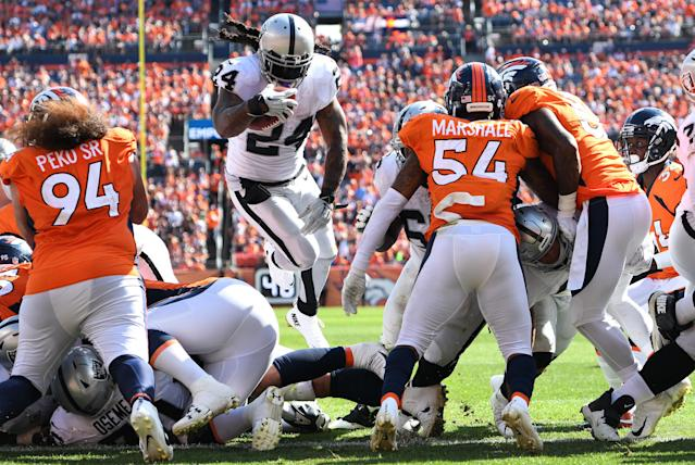 <p>Oakland Raiders running back Marshawn Lynch (24) leaps for a touchdown carry in the second quarter against the Denver Broncos at Broncos Stadium at Mile High. Mandatory Credit: Ron Chenoy-USA TODAY Sports </p>